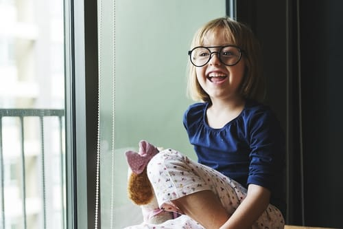 child with round glasses laughing by a window