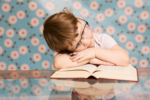 child with glasses resting on an open book