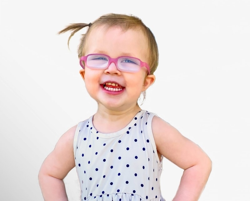 little girl with pink glasses smiling for children's charity